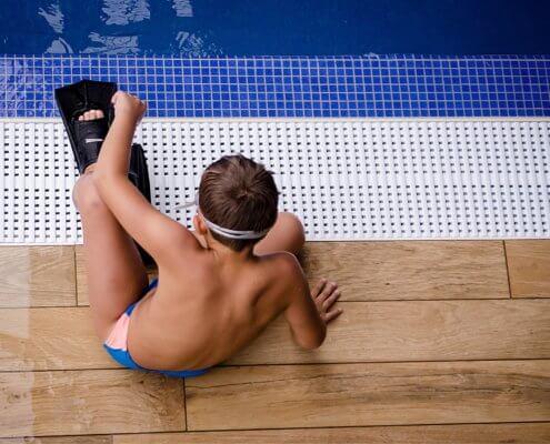 Junge sitzt am Pool mit Flossen und Tauchermaske