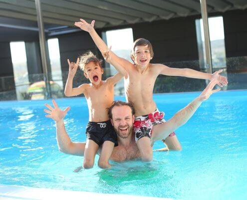 Vater und Kinder plantschen im Pool