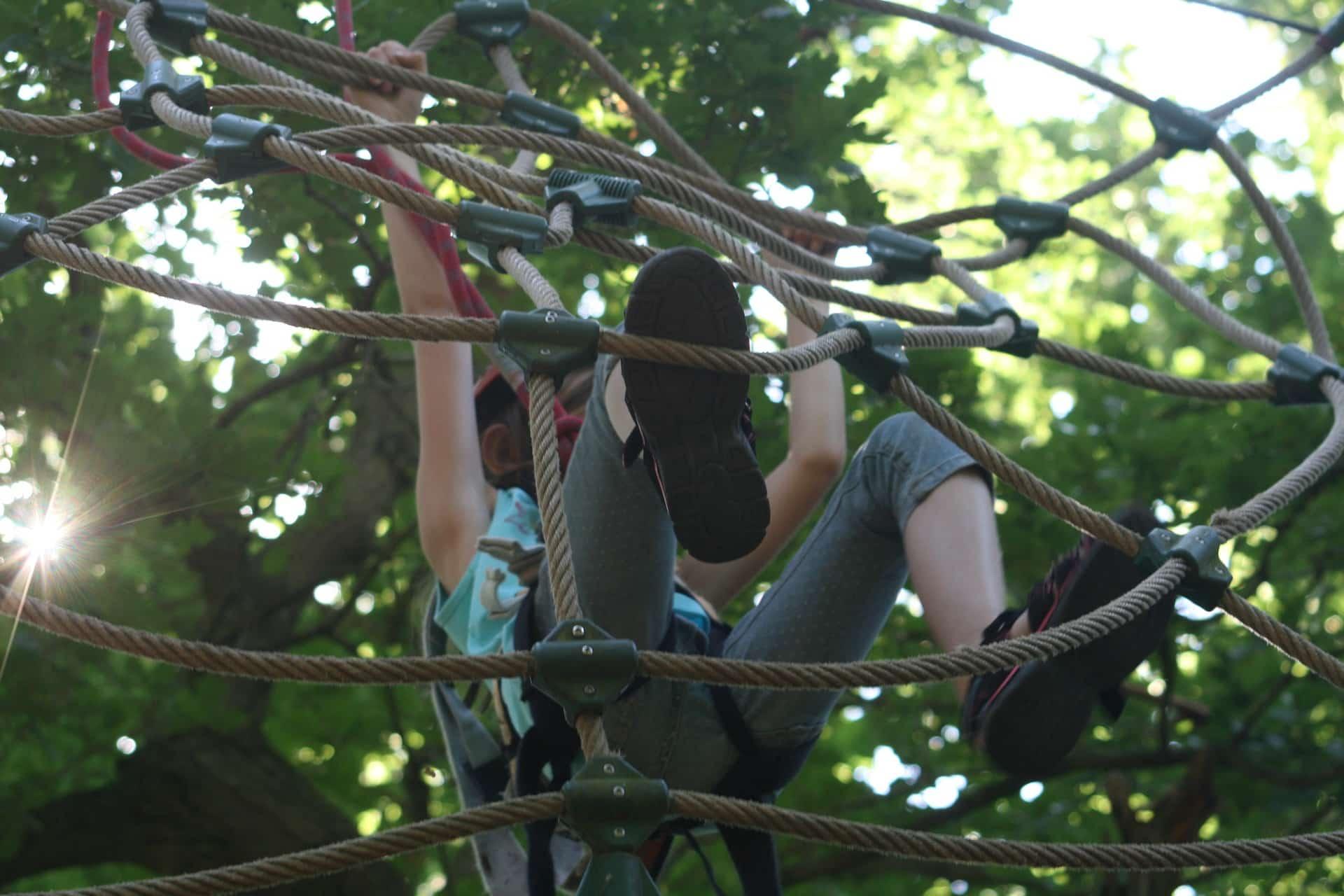 Mädchen im Kletterpark auf einem Seil-Spinnennetz im Freizeitpark Hessen