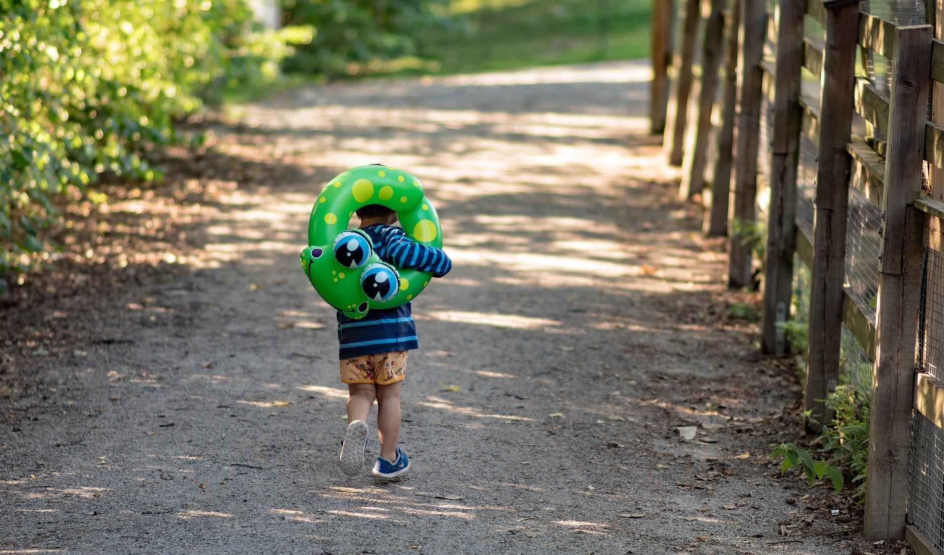 Junge mit grünem Schwimmreifen auf dem Weg zum Baden im Freizeitpark Hessen