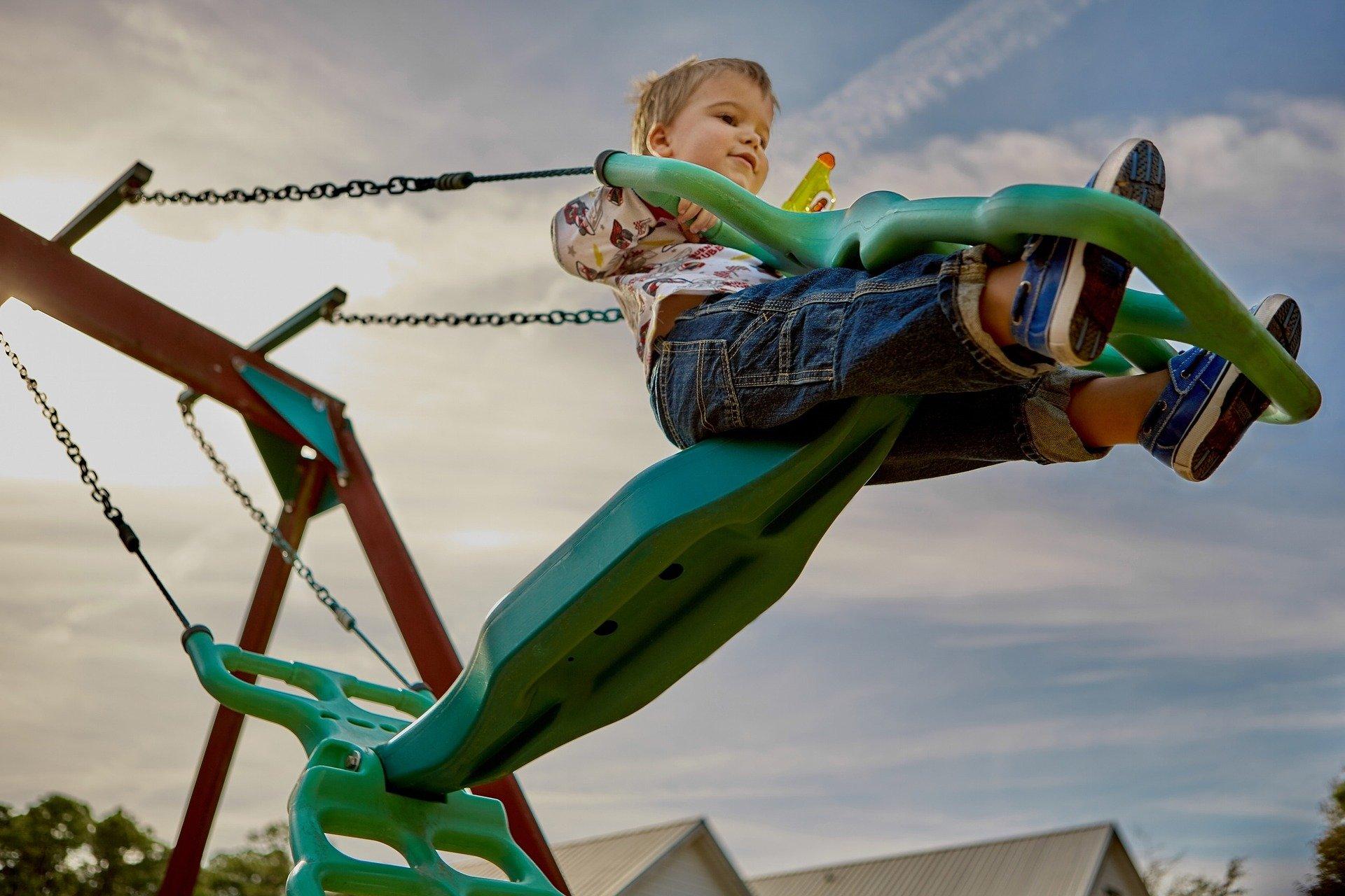 Kind auf einer grünen Schaukel mit einer Wasserpistole in der Hand im Freizeitpark Hessen