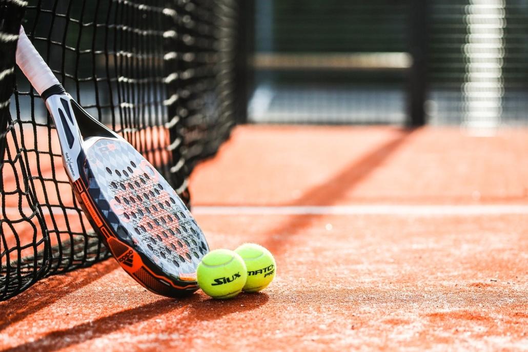 Tennisschläger- und Ball liegen auf dem Platz