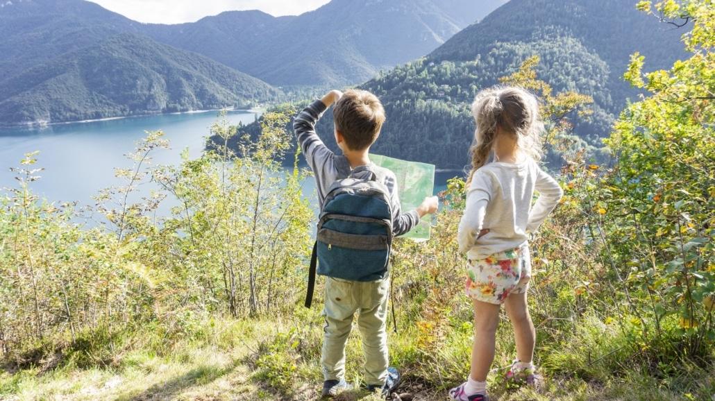 Zwei Kinder stehen an eine Aussichtspunkt und bestaunen die Natur