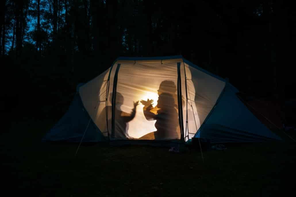 Kinder machen Schattenspiele im Zelt