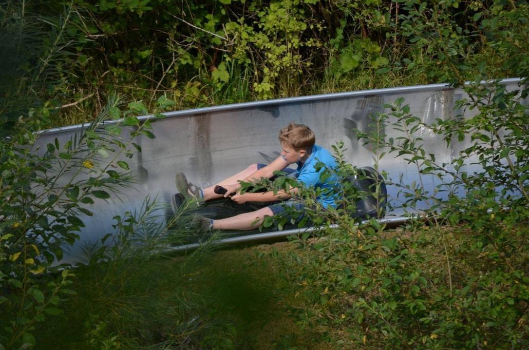 Junge saust die Rodelbahn im Wildpark hinunter